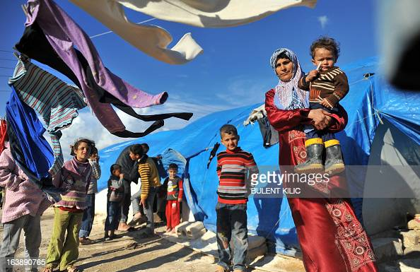 A Syrian woman carries her child outside their makeshift house at the refugee camp of Qah along the Turkish border in the village of Atme in the...