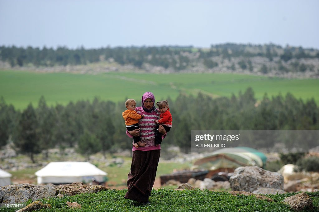A Syrian woman carries her children near their makeshift refugee camp at the mountains of the city of Afrin, on the Syria-Turkey border, on March 28, 2013. More than 70,000 people have died in Syria's two-year conflict, the UN says.