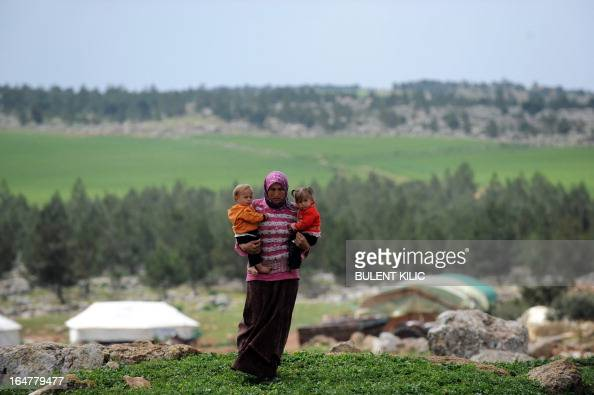 A Syrian woman carries her children near their makeshift refugee camp at the mountains of the city of Afrin on the SyriaTurkey border on March 28...