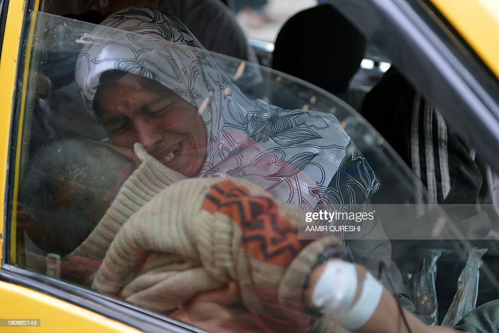 A Syrian woman cries holding her injured son in a taxi as they arrive at a hospital in northern city of Aleppo on February 8, 2013, following shelling by government forces. Loyalists troops made ground in the country's north, retaking Karnaz on the strategic Damascus-Aleppo highway on Wednesday after a 16-day onslaught, said Rami Abdel Rahman, head of the Syrian Observatory for Human Rights.