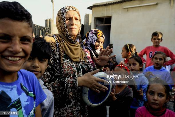 A Syrian woman drums on a tabla as she dances with children during the celebrations of the first wedding after the ouster of the Islamic State group...