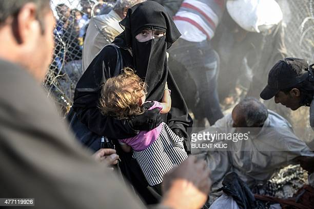 A Syrian woman fleeing the war carries her child as she passes through border fences to enter Turkish territory illegally near the Turkish border...