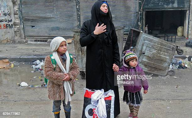 A Syrian woman fleeing violence in the restive Bustan alQasr neighbourhood reacts as she stands with her children in Aleppo's Fardos neighbourhood on...