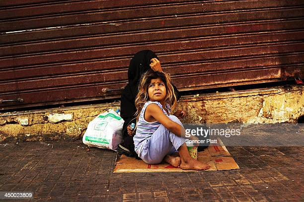 Syrian woman from the city of Damascus begs with her daughter in a wealthy district of Beirut on November 16 2013 in Beirut Lebanon As the war in...
