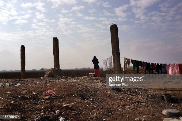 Syrian woman hangs laundry in a makeshift camp for Syrian refugees only miles from the border with Syria in the Bekaa Valley on November 12 2013 in...