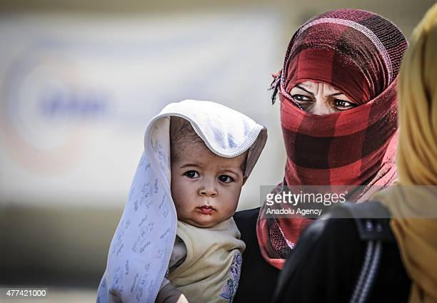 Syrian woman holds her baby in her arms as they return to the Syrian town of Tal Abyad from Turkey near Akcakale border crossing in Sanliurfa...