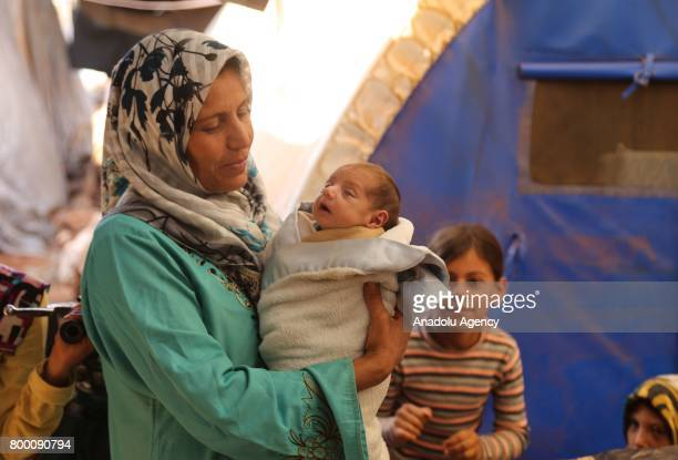 Syrian woman holds her baby in her arms near their tents during Muslim's holy month of Ramadan in Idlib Syria on June 23 2017 Ahead of Eid al Fitr...