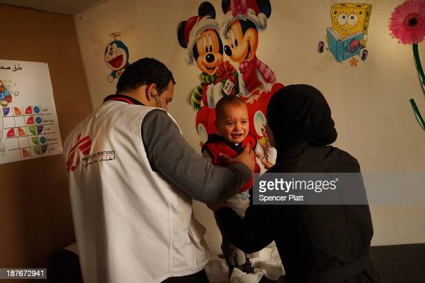 Syrian woman holds her child as he is examined by a doctor in a health clinic for refugees operated by Doctors Without Borders/Medecins Sans...