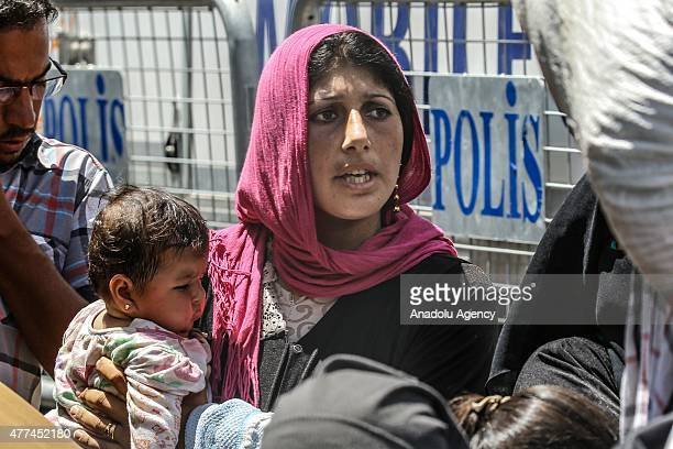 Syrian woman holds her daughter in her arms as they return to the Syrian town of Tal Abyad from Turkey near Akcakale border crossing in Sanliurfa...