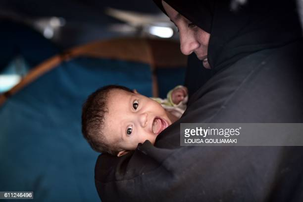 A Syrian woman holds her fourweek old baby at the municipalityrun Souda refugee camp on the island on Chios on September 29 2016 Greece is...
