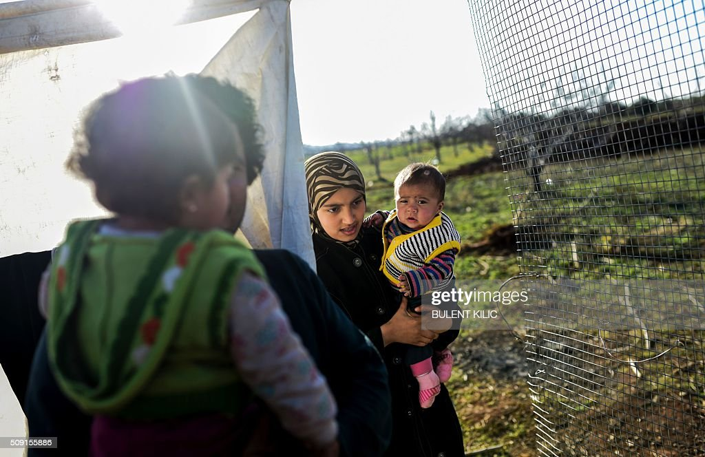 A Syrian woman living in a makeshift camp inside a farm holds her baby life near Oncupinar crossing gate, stand on February 9, 2016, in Kilis. Around 30,000 Syrians are at the Turkish border after fleeing a Russia-backed regime offensive on the northern region of Aleppo, Turkish Prime Minister Ahmet Davutoglu said on February 8, as his country faces mounting pressure to open its border. Davutoglu said the refugees would be admitted if need be, although Turkey should not be expected 'to shoulder the refugee issue alone.'. / AFP / BULENT KILIC