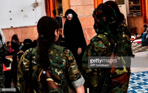 Syrian woman looks at fighters from the Syrian Democratic Forces as civilians gather on the western front after fleeing the centre of Raqa on October...