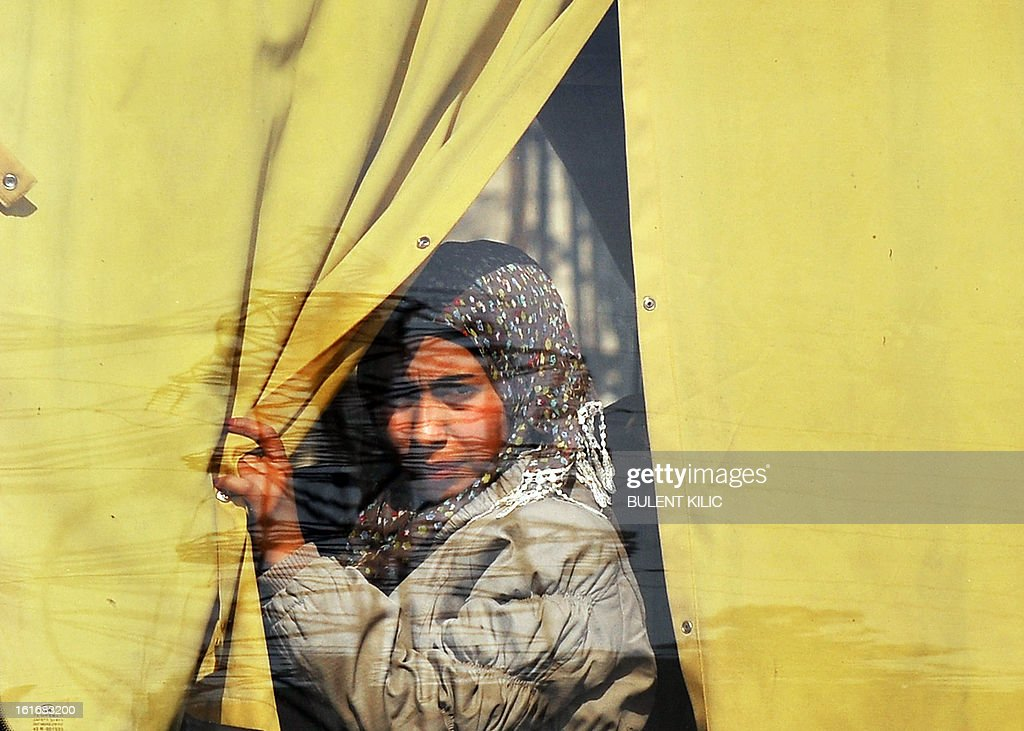 A Syrian woman looks through a bus window in the northern city of Aleppo on February 14, 2013. Syrian Foreign Minister Walid al-Muallem and opposition National Coalition chief Ahmed Moaz al-Khatib will make separate visits to Moscow for talks in the coming weeks, a top Russian diplomat said. AFP PHOTO/BULENT KILIC