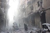 A Syrian woman makes her way through debris following an air strike by government forces in the northern city of Aleppo on July 15 2014 More than...