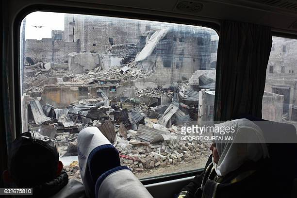 Syrian woman peers out the window as she sits in a train travelling through Aleppo's devastated eastern districts for the first time in more than...