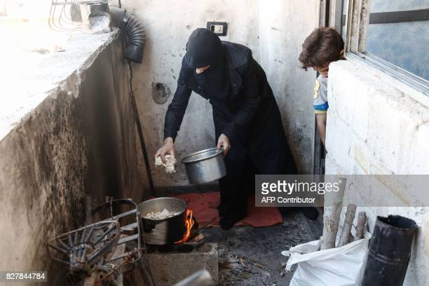 A Syrian woman prepares a meal using mushrooms as her son watches her in the rebelheld town of Douma on the eastern outskirts of Damascus on August 3...