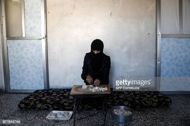 A Syrian woman prepares a meal using mushrooms in the rebelheld town of Douma on the eastern outskirts of Damascus on August 3 2017 Mushrooms are not...