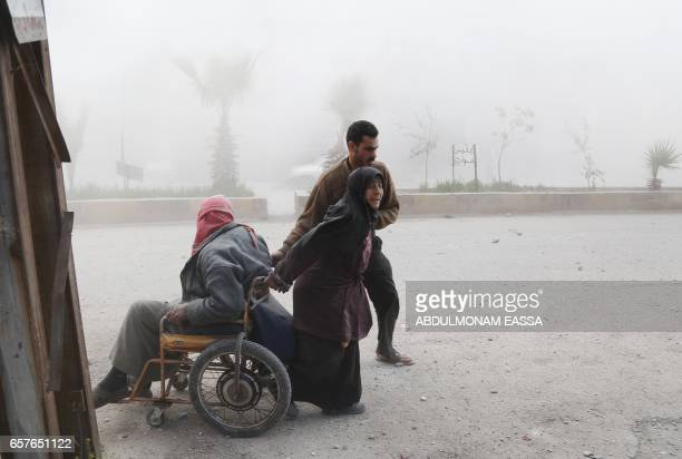 Syrian woman pulls her husband on a wheelchair as they evacuate from their home following a reported air strike on the rebelcontrolled town of...