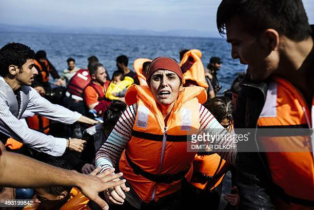 A Syrian woman reacts as she arrives with other refugees and migrants on the Greek island of Lesbos after crossing the Aegean sea from Turkey on...