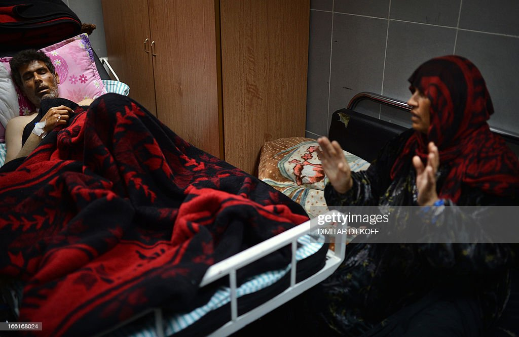 A Syrian woman sits at a hospital in the northern Syrian city of Afrin on April 9, 2013, next to her husband who was injured during an airstrike on the majority-Kurdish Sheikh Maqsud district of the northern city of Aleppo. Kurds comprise 10 percent of Syria's total population, with most living in the north of the embattled country.