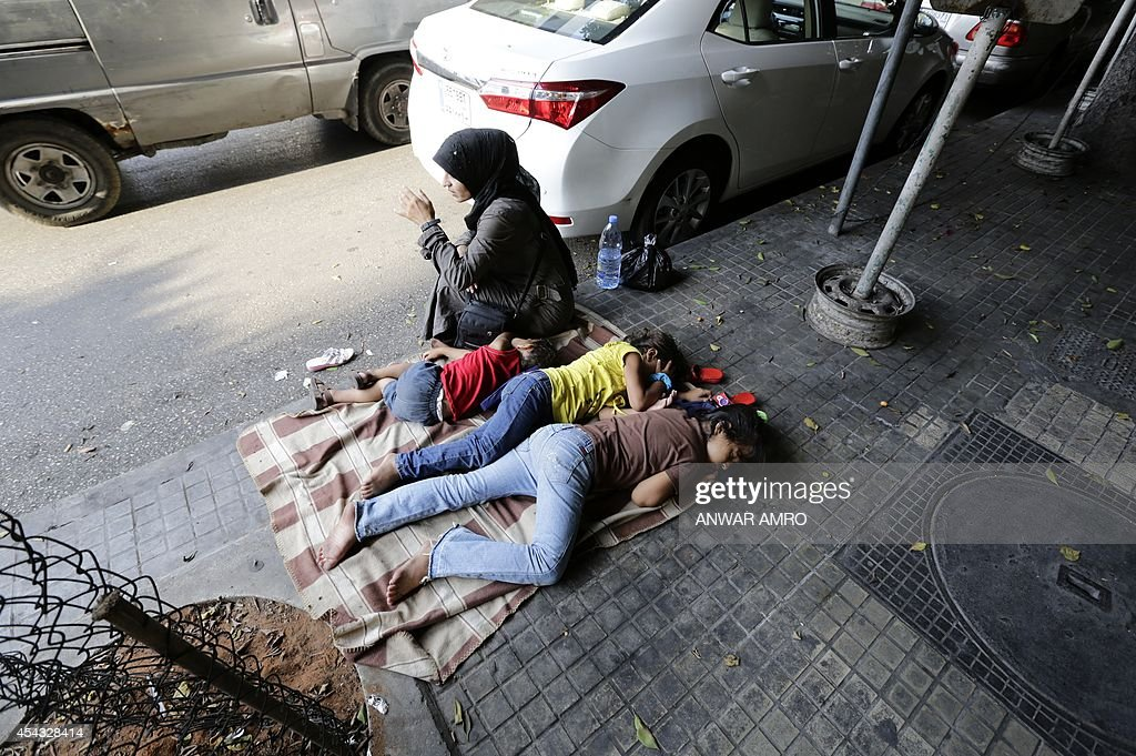 A Syrian woman sits next to her children sleeping on the street in Hamra Street in the Lebanese capital Beirut on August 29 2014 The number of...