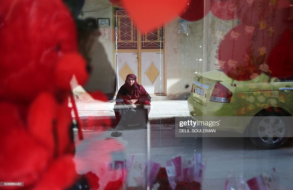 A Syrian woman sits outside a shop displaying Valentine's day gifts in the northeastern city of Qamishli on February 13, 2016. / AFP / DELIL SOULEIMAN