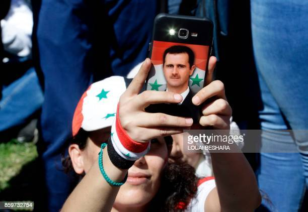 A Syrian woman takes a photo on her phone bearing a portriat of the Syrian president in Umayyad Square in Damascus as fans gathered to watch a live...