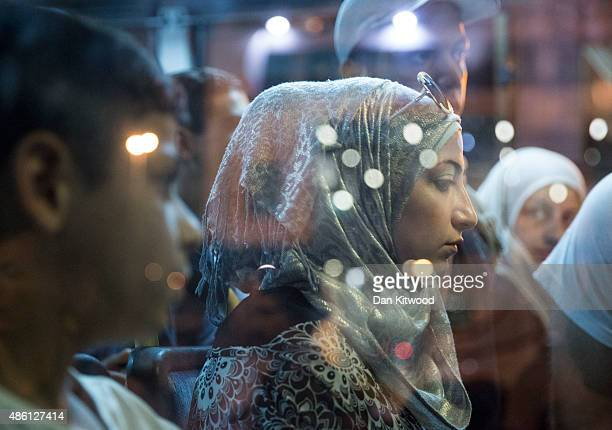 Syrian woman waits on a bus heading to Athens Train Station as migrants disembark along with European tourists from a Blue Star ferry on the Greek...