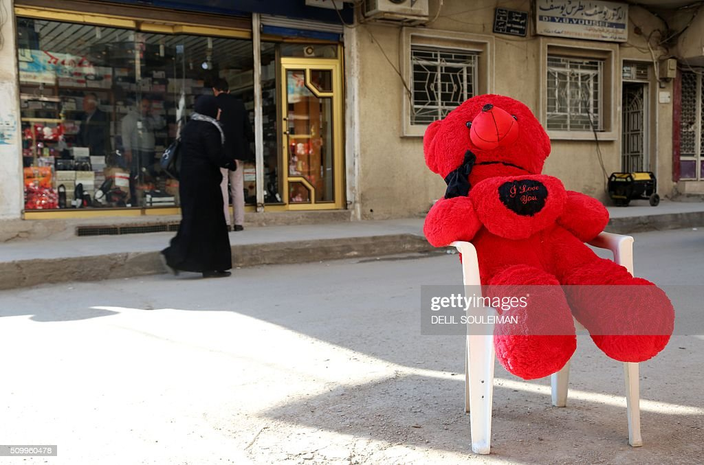A Syrian woman walks past a man-sized teddy bear as shops display Valentine's day gifts in the northeastern city of Qamishli on February 13, 2016. / AFP / DELIL SOULEIMAN