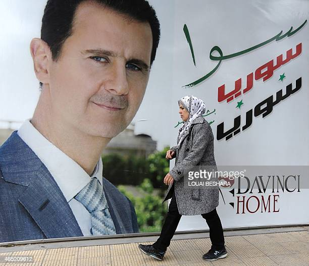 A Syrian woman walks past a placard bearing a portrait of President Bashar alAssad in the city of Damascus on March 4 2015 AFP PHOTO / LOUAI BESHARA