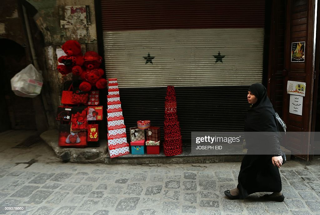 A Syrian woman walks past a shop displaying red teddy bears and gifts for Valentine's day in Damascus on February 10, 2016. / AFP / JOSEPH EID