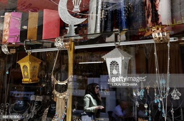 A Syrian woman walks past a shop displaying traditional lanterns known in Arabic as 'Fanous' sold during Ramadan in the old city of Damascus on May...