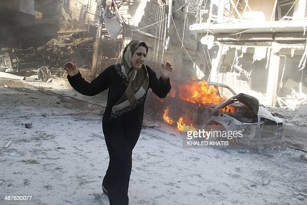 A Syrian woman walks past the burning wreckage of a car following reported air strikes by government forces on May 1 2014 in the Halak neighbourhood...