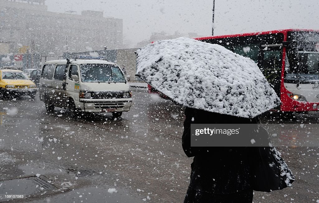 A Syrian woman walks through central Damascus during snow fall on January 9, 2013 as a fierce storm whipped the region this week and temperatures dropped dramatically.