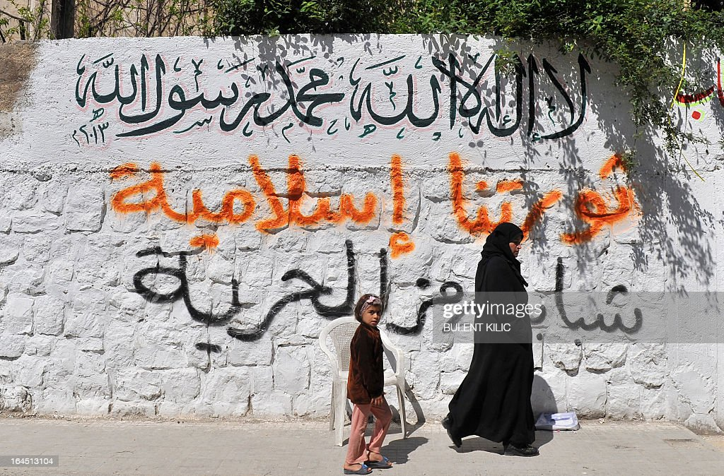 A Syrian woman walks with her daughter passed a wall with graffiti written on it, in the northern city of Aleppo on March 24, 2013. Syria's mainstream insurgent Free Syrian Army does not recognise Ghassan Hitto, a rebel prime minister chosen by dissidents after hours of heated talks last week, a rebel official told AFP. Arabic writings on wall read 'There is no God but God and Mohammed is the prophet of God, Our revolution is Islamic, our youth are the symbol of freedom'. AFP PHOTO/BULENT KILIC