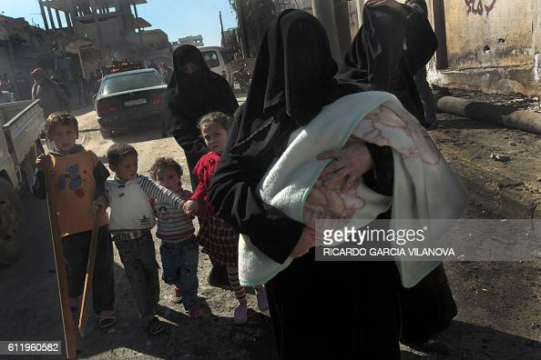 Syrian women and their children flee the violence in the northwestern city of Sermin on March 24 2012 shortly before government security forces...