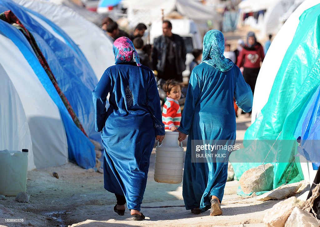 Syrian women carry a water jug back to their makeshift house at the refugee camp of Qah along the Turkish border in the village of Atme in the northwestern province of Idlib, on March 17, 2013. The conflict has killed at least 70,000 people, and forced more than one million Syrians to seek refuge abroad. Millions more have been internally displaced.