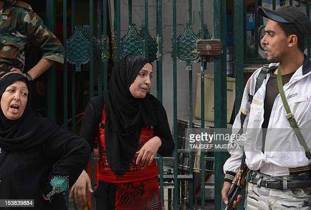 Syrian women cry outside a hospital following an air strike by regime forces in the northern city of Aleppo on October 9 2012 Syrian rebels took...