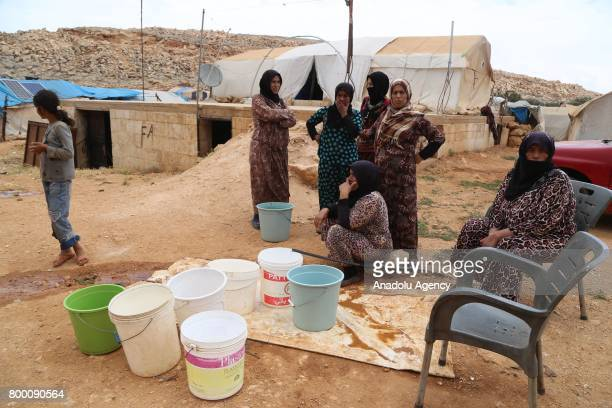 Syrian women fill their buckets with water during Muslim's holy month of Ramadan in Idlib Syria on June 23 2017 Ahead of Eid al Fitr Syrian people...
