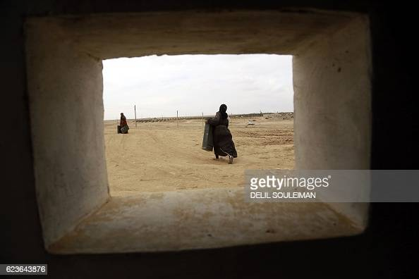 TOPSHOT Syrian women gather empty ammunition boxes used during the ongoing offensive by the KurdishArab alliance known as the Syrian Democratic...
