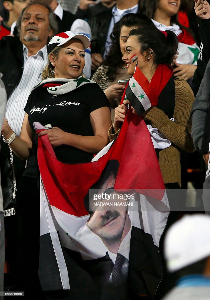 Syrian women hold their national flag bearing the image of embattled President Bashar al-Assad during their country's team football match against Iraq in the 7th West Asia Football Federation (WAFF) championship in Kuwait City on December 13, 2012.