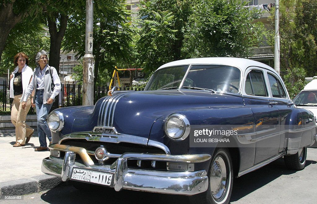 Syrian women pass by a 1953 Pontiac parked in one of Damascus' residential neighborhoods 20 May 2004. Old cars from the 1950s and 60s are not a rare sight in the Syrian capital, where taxes on new cars can go as high as 500 percent which makes them out of reach for ordinary Syrians. AFP PHOTO/Louai BESHARA