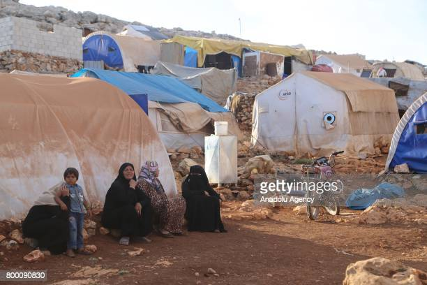 Syrian women sit on rocks outside of tents during Muslim's holy month of Ramadan in Idlib Syria on June 23 2017 Ahead of Eid al Fitr Syrian people...