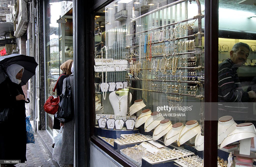 Syrian women stand outside a jewellery store in Damascus on November 11, 2012. After nearly 20 long months of conflict, many Syrians are now digging deep into their pockets, with many having to sell their jewellery -- including family heirlooms -- just to survive.