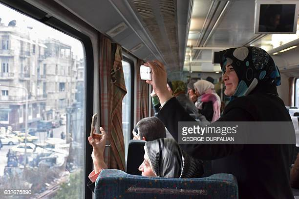 TOPSHOT Syrian women take pictures as they ride a train travelling through Aleppo's devastated eastern districts for the first time in more than four...