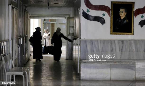 Syrian women walk in a hospital decorated with a portrait President Bashar alAssad in the eastern city of Deir Ezzor on September 20 2017 as Syrian...