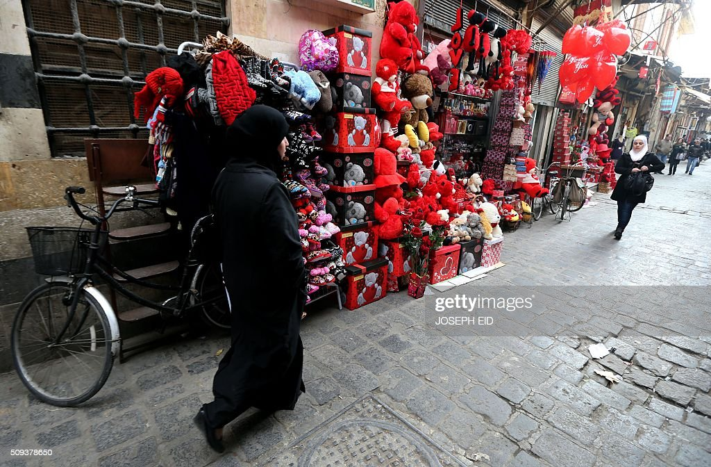 Syrian women walk past shops displaying red teddy bears, balloons and gifts for Valentine's day in Damascus on February 10, 2016. / AFP / JOSEPH EID