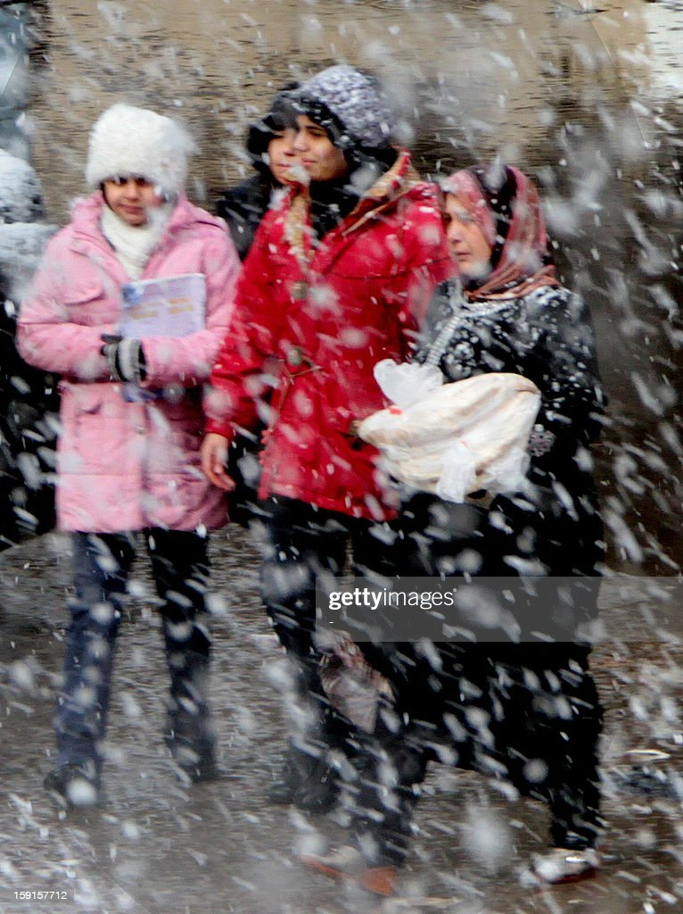 Syrian women walk through the streets of central Damascus during snow fall on January 9, 2013 as a fierce storm whipped the region this week and temperatures dropped dramatically.