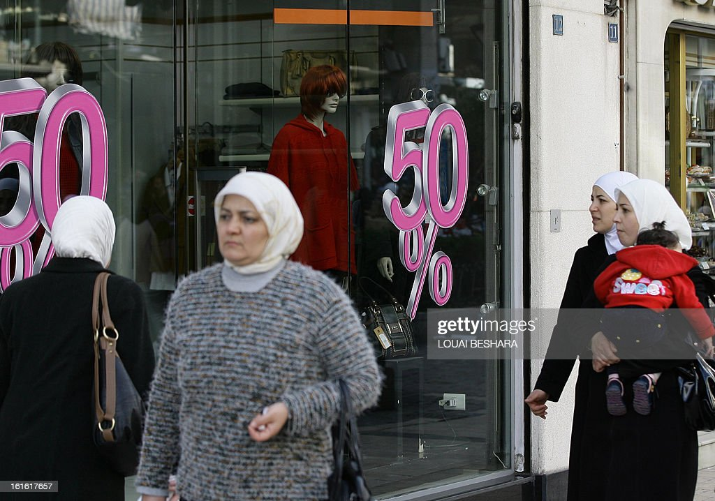 Syrian women was past a shop advertising discounts at a souq in Damascus on February 13, 2013. Syria's state news agency SANA cited electricity minister Imad Khamis as saying widespread blackouts have caused economic losses of around $2.2 billion since March 2011. AFP PHOTO/LOUAI BESHARA