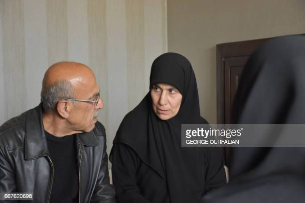 Syrian women who had been held prisoner by opposition forces are greeted by relatives in alHamdaniyah in eastern Aleppo on April 12 upon their...